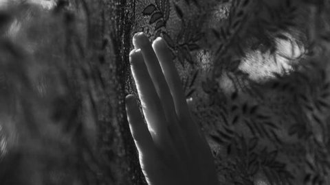 Closeup woman's hand touching black lace curtain - black and white video in slow motion