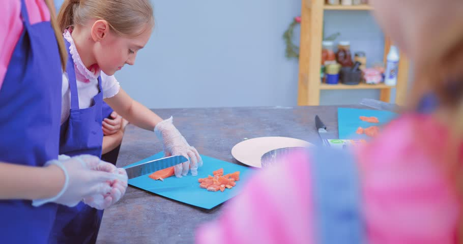 Girl child is cutting fish on a kitchen board. A child is cutting salmon on a kitchen table | Shutterstock HD Video #1011485393