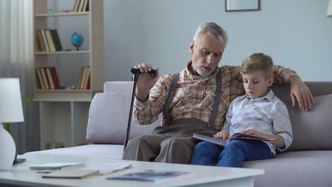 Grandpa watching photo album with grandson, remembering youth, telling stories