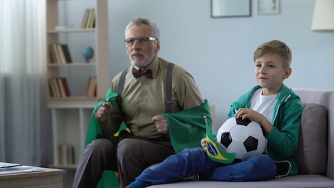 Grandpa waving Brazil flags together with grandson, watching football at home