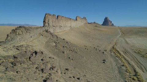 Fly along 150' high volcanic dike to Ship Rock in New Mexico