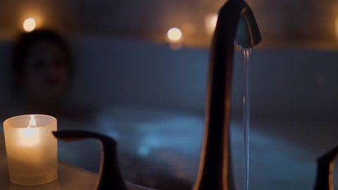 Female Taking a Candlelit Bath Laying Move Left. a slow motion view of a female taking a bath by candle light, focus on foreground bath faucet and candles