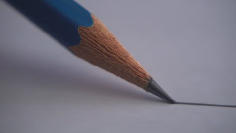 The artist drawing a flat line with a graphite pencil pencil. Artists hands drawing wooden pencil writes line on paper.