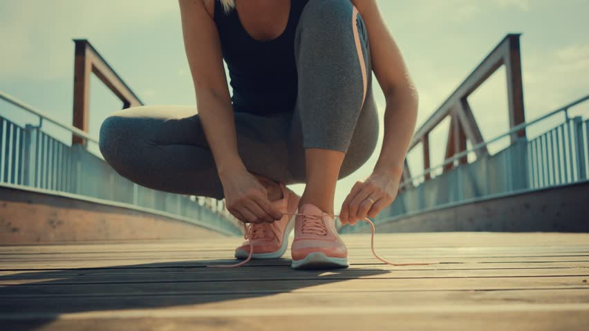 Running woman. Girl run and jogging training close-up sneakers in bridge background in sunny day | Shutterstock HD Video #1011557093