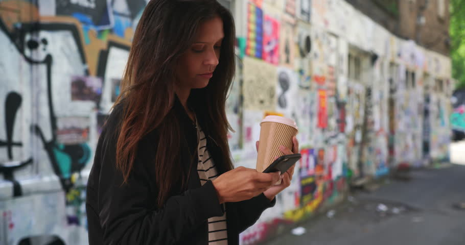 Hipster girl in bomber jacket texting with cellphone in graffiti alley. Smiling female with her coffee on urban street with street art messaging friend with smartphone. 4k