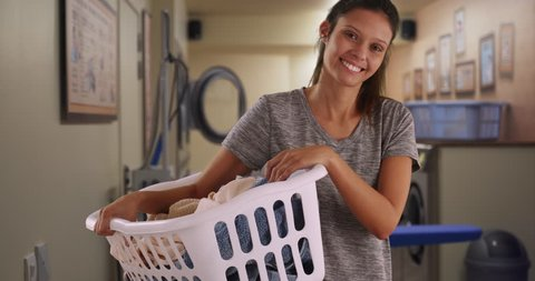 Cheerful young woman holding basket of clothes in laundry room. Young mom or housewife washing and ironing clothes at home posing for portrait. 4k
