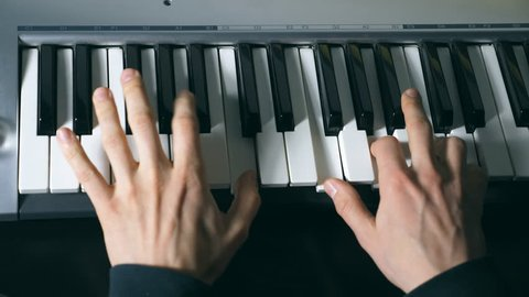 Hands of male musician playing at synthesizer. Mens arms plays solo of music or new melody. Close up fingers of pianist at the piano keys. Slow motion Top view Isolated shot