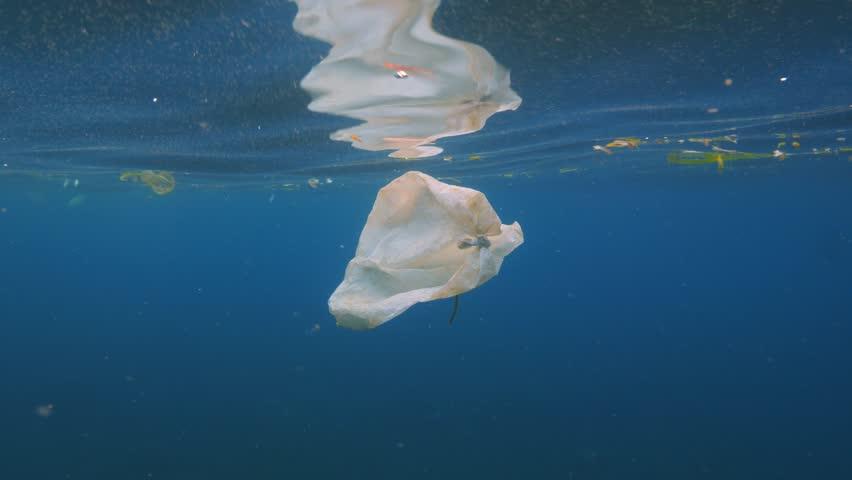 Environmental problem, plastic bag in  ocean water on blue background