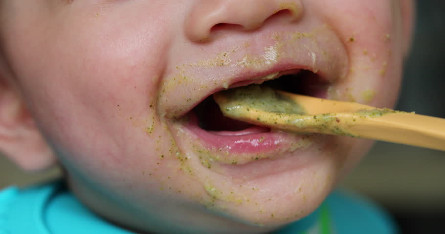 close-up face cute baby eating meal puree with mother #1011659333