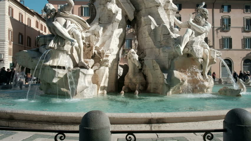 Slow low angle camera tilt up from marble sculptures of Fiumi Fountain to Egyptian obelisk top at the center water fountain of Piazza Navona. 4K UHD at 29.97fps