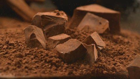 Chunks of chocolate falling into powdered chocolate, shot with Phantom Flex