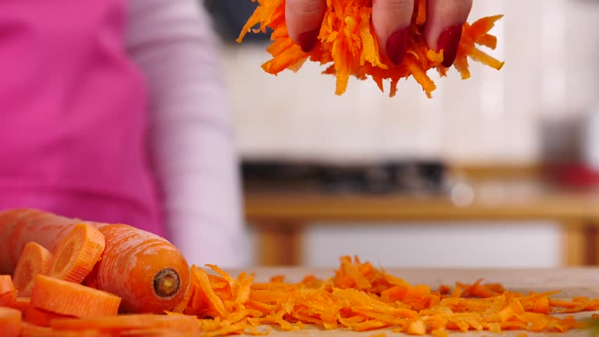 Unrecognizable woman hand playing with grat carrot making it rain. Close up in slow motion.