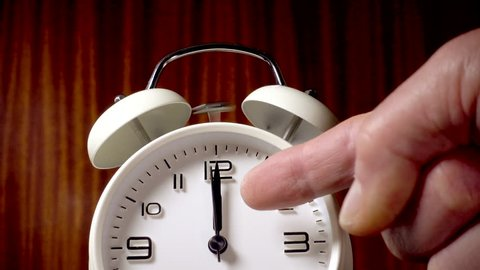 Time related concept: Slow motion shot of a man's hand putting down a traditional alarm clock, then pointing with a finger just as the time reaches 12-o-clock, with the alarm hammer ringing the bells.
