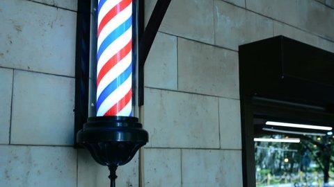 Barber pole rotating on wall in hairdresser shop. Barber pole spinning at barbershop. Vintage barbershop and hairdresser symbol. Traditional barber pole rotating in barbershop