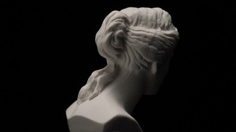 Ancient roman era white marble statue of Venus rotating and showing every angles. Closeup shot with black background.