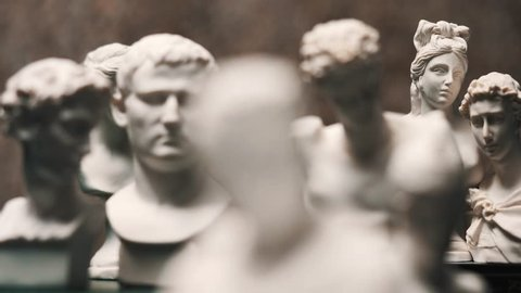 Focus changing between many famous roman sculptures busts made of marble. Closeup shots with focus pull.