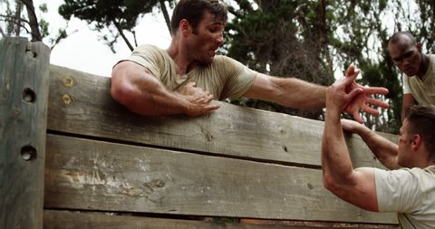 Male soldiers assisting their team mate to climb a wooden wall at boot camp 4k
