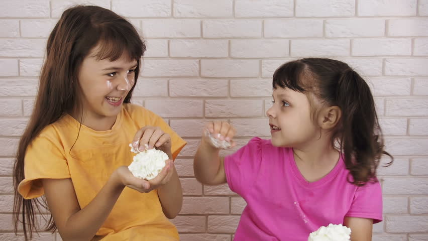 Funny children. Children with a cream custard. Sisters play with a food cream.