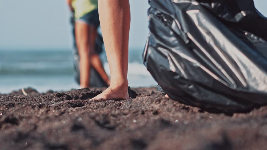 Group of volunteers cleaning up beach. The volunteer raises and throws a plastic bottle into the bag. Volunteering and recycling concept. Environmental awareness concept copy space | Shutterstock HD Video #1011722213