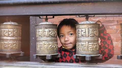 A cute little Tibetan boy playing with the prayer wheels in Buddhist temple. A adorable but poor kid playing with prayer wheels in a Buddha or Buddhist monastery in Nepal