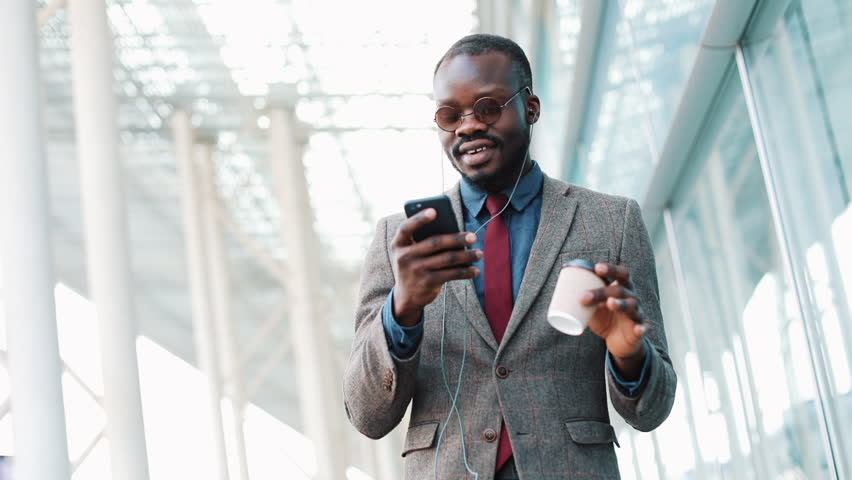 Happy african american businessman listening to music in headphones on smartphone, walking outside the office and funny dancing to the rythm. Drink coffee, funny dancing moves. Close up, slow motion #1011733373