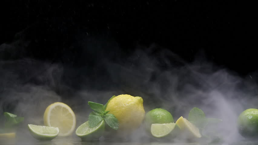 Tropical lemon and lime cuts in cold ice clouds of fog under water spray droplets on black background | Shutterstock HD Video #1011736913