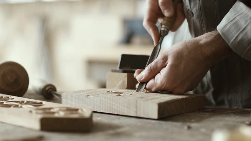 Professional carpenter working in his workshop and carving wood using a gouge, woodworking and craftmanship concept | Shutterstock HD Video #1011737543