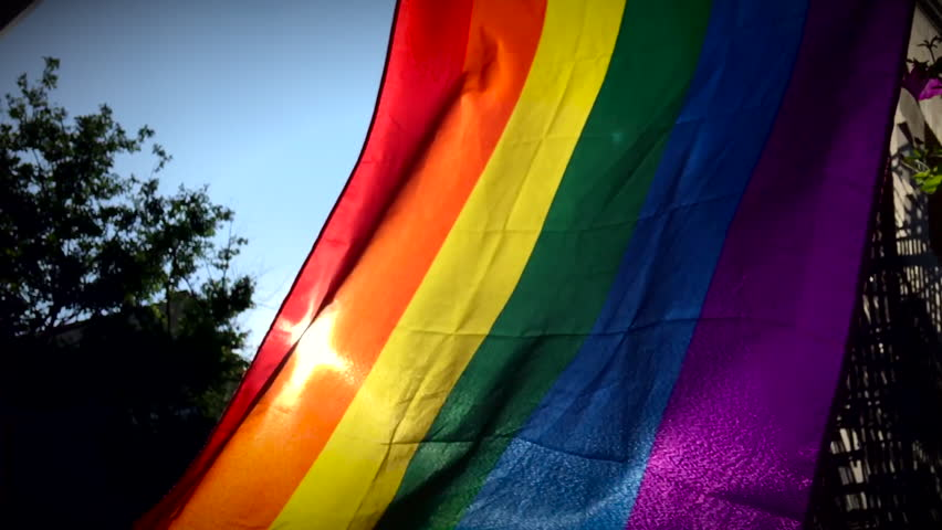 Gay pride rainbow flag flying backlit by the summer sun in the tolerant neighborhood of Greenwich Village in New York City | Shutterstock HD Video #1011738803