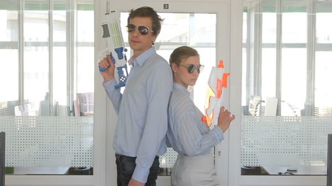 crop close up view of young man and woman standing in sunglasses backs to each other with toy pistols in office