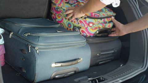 SLOW MOTION, CLOSE UP: Unrecognizable male tourist packing his and his girlfriend's bags in the back of a spacious black car. Unknown man putting baggage in black car parked in the sunny driveway.