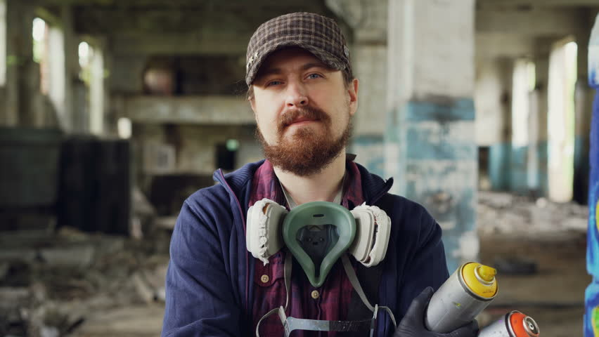 Close-up portrait of handsome bearded man graffiti artist standing inside abandoned building wearing cap, gloves and pespirator and holding spray paint