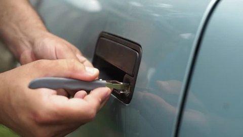 Male Mechanic Holding Lockpicker To Open  Car Door