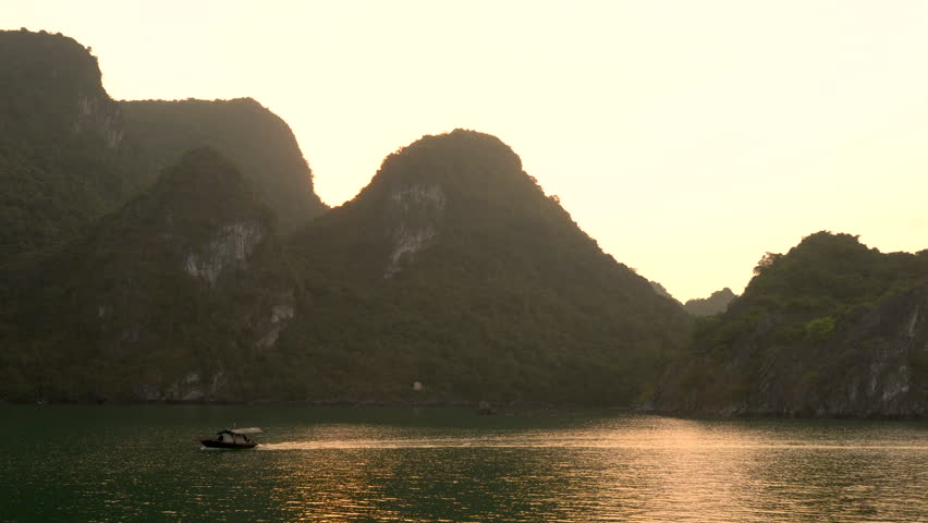 Traditional fishing boat sailing at sunset through the limestone islands in UNESCO World Heritage site, Ha Long Bay, Cat Ba National Park, Vietnam