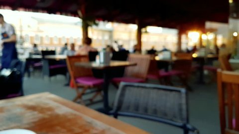Blur image or defocus of customer in coffee shop. Blurred picture of interior of large beautiful restaurant with bright lighting. Defocused restaurant