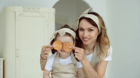 Mama covers her little daughter's eyes with cookies. A happy family.