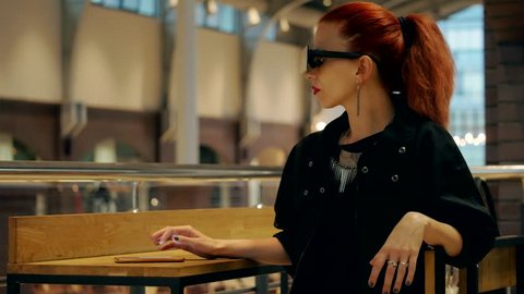 Stylish red hair woman with square sunglasses watches mobile phone in the mall