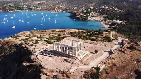 Aerial drone bird's eye view video of boats docked near iconic archaeological site of Cape Sounio, Ancient temple of Poseidon, Attica, Greece