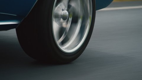 Close up of back wheel blue car driving on road in daylight