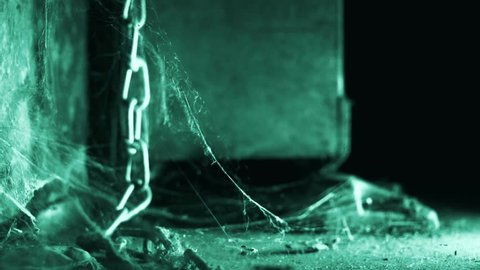 Close up of big door opening and closing behind a hanging old chain with spider web in slowmotion.