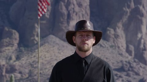 Cowboy proudly standing in front of mountains and flag