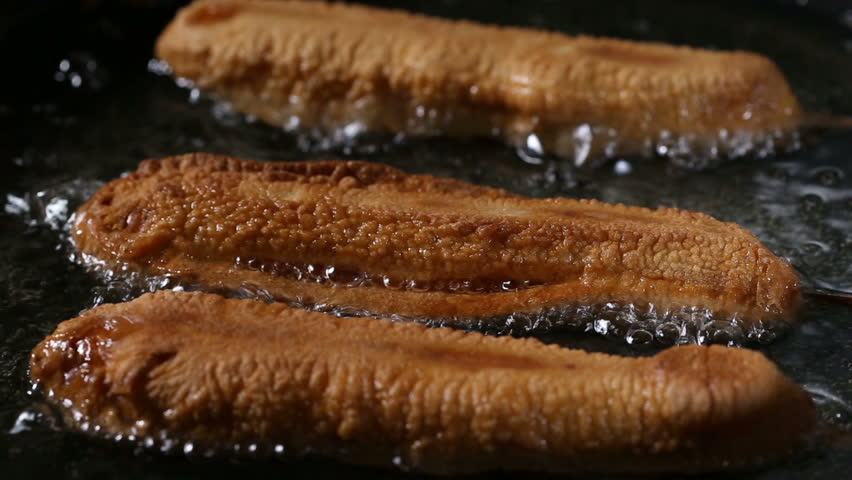 Corn Dogs - Frying in pan with sunflower oil - close up view