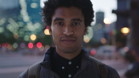 close up portrait of handsome young mixed race man smiling cheerful at camera enjoying calm urban evening in city commuting travel lifestyle