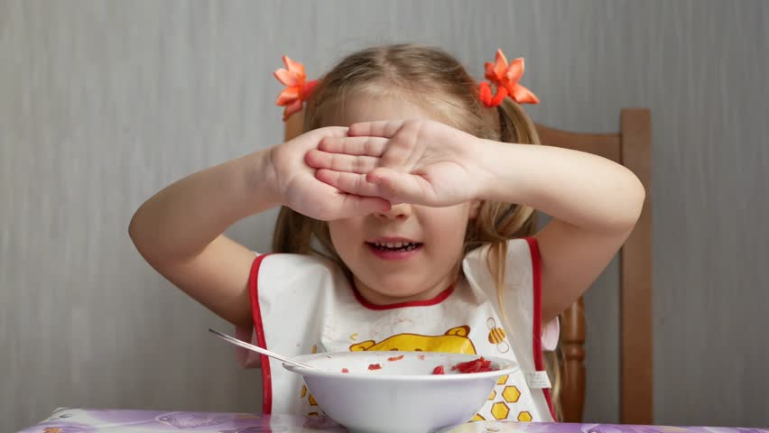 Funny little blue-eyed girl with blond hair is played and shows her fingers like a cow's horns at home kitchen