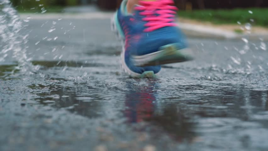 Close up slow motion shot of legs of a runner in sneakers. Female sports man jogging outdoors in a park, stepping into muddy puddle. #1011997943