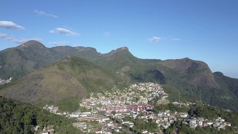 Aerial view of Petropolis, city in the middle of the mountains in Brazil, near Rio de janeiro. Beautiful day with blue sky and sun in the green trees of tropical forest.