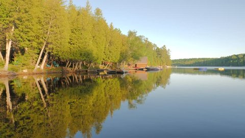 Various shots and angles from a lakeview cottage property up north at sunset, featuring scenic views of camping and lake side settings such as boating, camp fires, sand, beach, and tree lines.