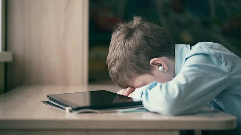 The child fell asleep while he was doing his homework, listening to the audiobook.