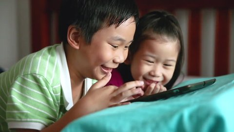 Asian children using digital tablet. Happily brother smiling and cheering his younger sister near by. Cute girl playing games excitedly on touchpad and lying prone on bed. Focus shifting from boy to g