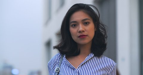 Close up of one young asian woman looking at camera smile in the street, 4k