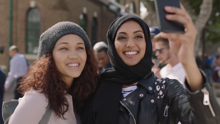 Portrait of two young woman friends close up of multi ethnic girlfriends posing making faces taking selfie photo using smartphone enjoying hanging out | Shutterstock HD Video #1012052483